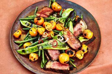 Filete de tira a la parrilla con tomates y judías verdes.